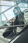 Stilvolle Frau benutzt Handy im Treppenhaus — Stockfoto