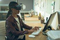 Виконавчої влади, які працюють на комп'ютері під час використання віртуальної реальності гарнітуру в офісі — стокове фото