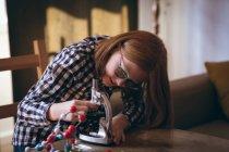 Fille faire des expériences au microscope à la maison — Photo de stock