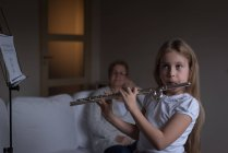 Girl playing flute in living room at home — Stock Photo