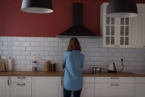Вид сзади женщины, работающие на кухне дома — стоковое фото