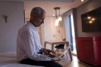 Homme d'affaires à l'aide d'un ordinateur portable sur le lit dans la chambre d'hôtel — Photo de stock