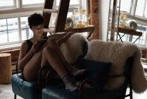 Belle femme utilisant une tablette numérique tout en se relaxant sur la chaise n salon — Photo de stock