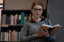 Молодая женщина, читающая книгу в библиотеке — стоковое фото