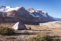 Vista posteriore della donna che si siede vicino alla tenda un giorno pieno di sole — Foto stock
