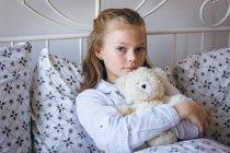 Portrait de fille jouant tenant ours en peluche sur le lit — Photo de stock
