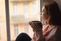 Femme prenant un café tout en regardant par la fenêtre à la maison — Photo de stock