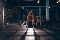 Donna in forma sollevare il bilanciere in palestra — Foto stock