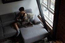 Vue grand angle de belle femme utilisant une tablette numérique tout en se relaxant sur le canapé — Photo de stock