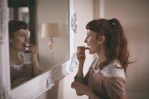 Femme appliquant du rouge à lèvres devant le miroir à la maison — Photo de stock