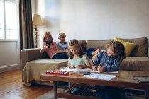 Sœurs faisant leurs devoirs dans le salon à la maison — Photo de stock