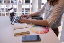 Sección media del ejecutivo femenino usando el ordenador portátil en el escritorio en la oficina - foto de stock