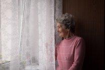 Femme âgée debout près de la fenêtre à la maison — Photo de stock