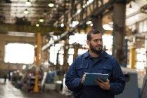 Techniker hält Rekord auf Klemmbrett in Metallindustrie — Stockfoto