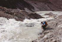 Чоловічий мандрівного миття рук в річці сонячний день — стокове фото