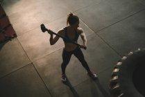 Мускулистая женщина бьет колесо колеса кувалдой в спортзале — стоковое фото