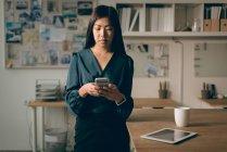 Executivo feminino usando o celular no escritório — Fotografia de Stock