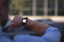 Чоловік дивиться на smartwatch в міській вулиці — стокове фото