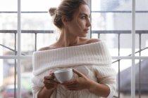 Femme réfléchie ayant du thé vert à la maison — Photo de stock