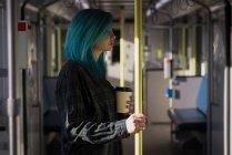 Élégante femme tenant la tasse de café pendant un voyage en train — Photo de stock