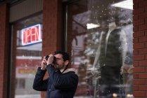 Mann Klick Foto mit Digitalkamera vor dem Geschäft — Stockfoto