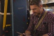 Homme écoutant de la musique sur tablette numérique tout en voyageant en tram — Photo de stock