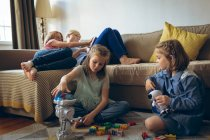 Siblings playing with toys in living room at home — Stock Photo