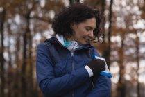 Молодая женщина использует мобильный телефон с браслетом в парке — стоковое фото