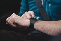 Mezzo sezione di uomo utilizzando smartwatch in una macchina — Foto stock