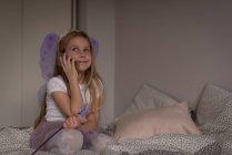 Fille parlant sur téléphone portable dans la chambre à coucher à la maison — Photo de stock