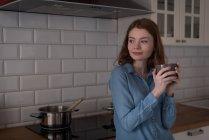 Réfléchie femme debout avec une tasse de café dans la cuisine — Photo de stock