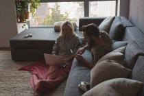 Pareja usando portátil y tableta digital en la sala de estar en casa - foto de stock