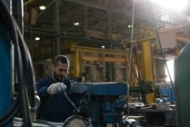 Aufmerksamen Techniker in Schutzkleidung arbeiten in der Metallbranche — Stockfoto