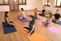 Groupe de personnes méditant ensemble dans un club de fitness — Photo de stock