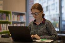 Молодая женщина с ноутбуком в библиотеке — стоковое фото
