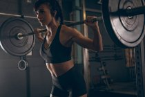 Fit woman lifting the barbell in the gym — Stock Photo