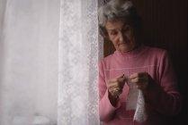 Femme âgée active tricot laine à la maison — Photo de stock