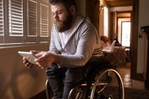 Disabled man using digital tablet at home — Stock Photo