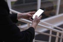 Section médiane du graphiste femelle à l'aide de téléphone portable au bureau — Photo de stock