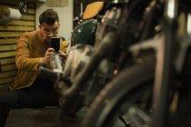 Механік беручи малюнок мотоцикл з мобільного телефону в гаражі — стокове фото