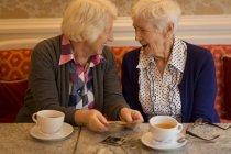 Старшие друзья общаются друг с другом за чашечкой кофе дома — стоковое фото