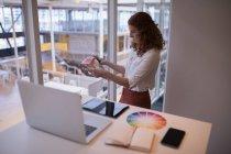 Diseñadora gráfica femenina mirando el libro de muestras de color en la oficina - foto de stock
