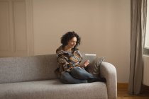 Woman using digital tablet in living room at home — Stock Photo