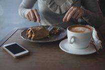 Средняя секция женщины с ложкой и вилкой в кафе — стоковое фото