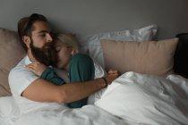 Pareja abrazándose en el dormitorio en casa - foto de stock