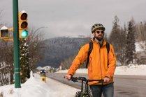 Человек, идущий на велосипеде по тротуару зимой — стоковое фото