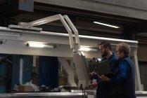 Techniciens opérant machine dans l'industrie métallurgique — Photo de stock
