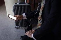 Section médiane de l'homme d'affaires à l'aide d'un téléphone intelligent dans la chambre d'hôtel — Photo de stock