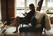Femme utilisant un téléphone portable tout en prenant un café à la maison — Photo de stock