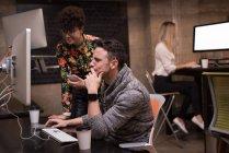 Чоловічі і жіночі виконавчої обговорювати над комп'ютером в офісі — стокове фото